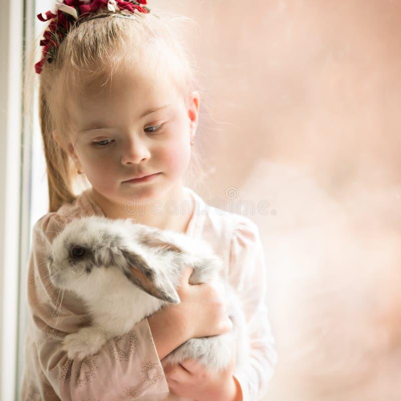 Девушка с Синдромом Дауна обнимает кролика стоковые фото
