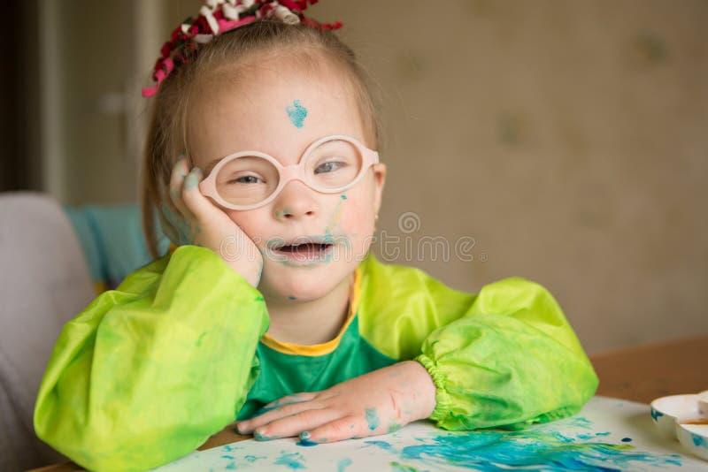 Девушка с Синдромом Дауна рисует краски стоковые фото