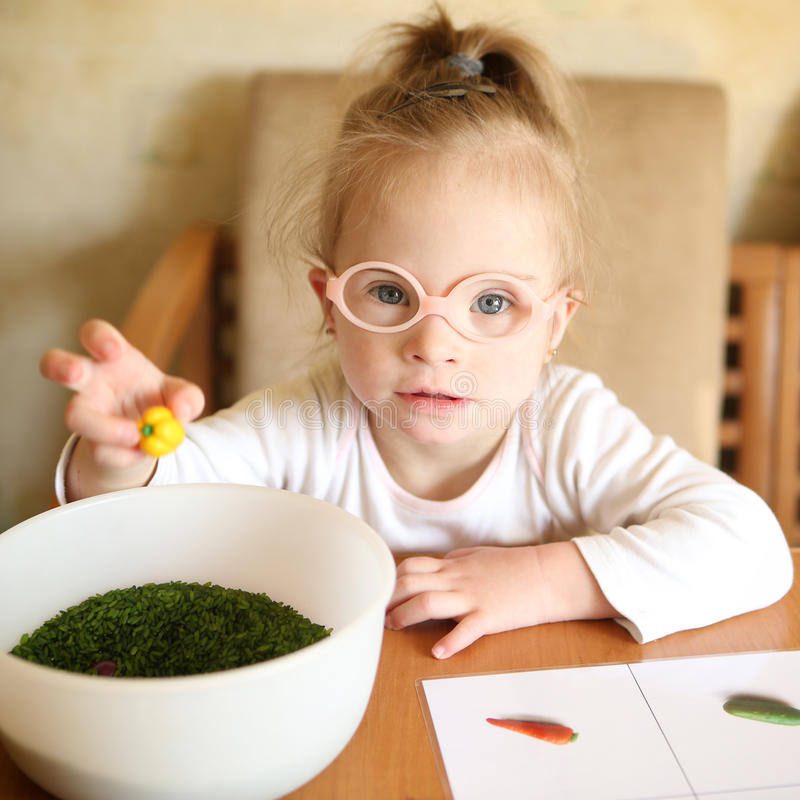 Девушка с Синдромом Дауна включается в сортировать овощи стоковая фотография