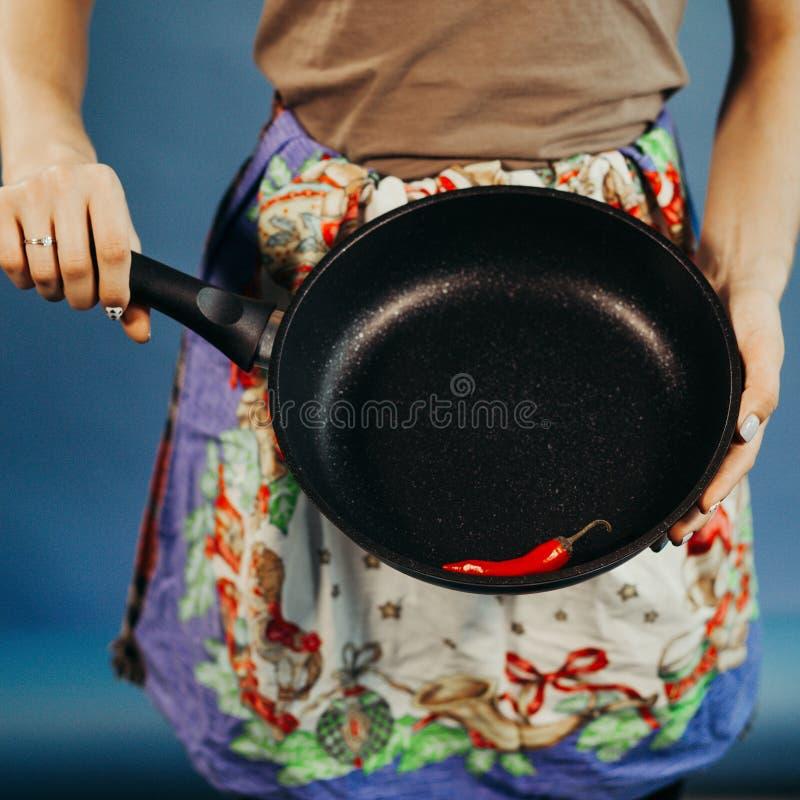 Девушка с сковородой Красный острый перец Чили на сковороде стоковые фото