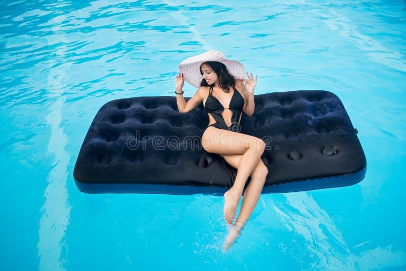 Девушка с совершенной диаграммой в черных бикини и шляпе лежа на тюфяке в бассейне стоковые фотографии rf