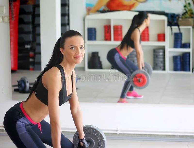 Девушка с совершенным телом в зале фитнеса стоковая фотография rf