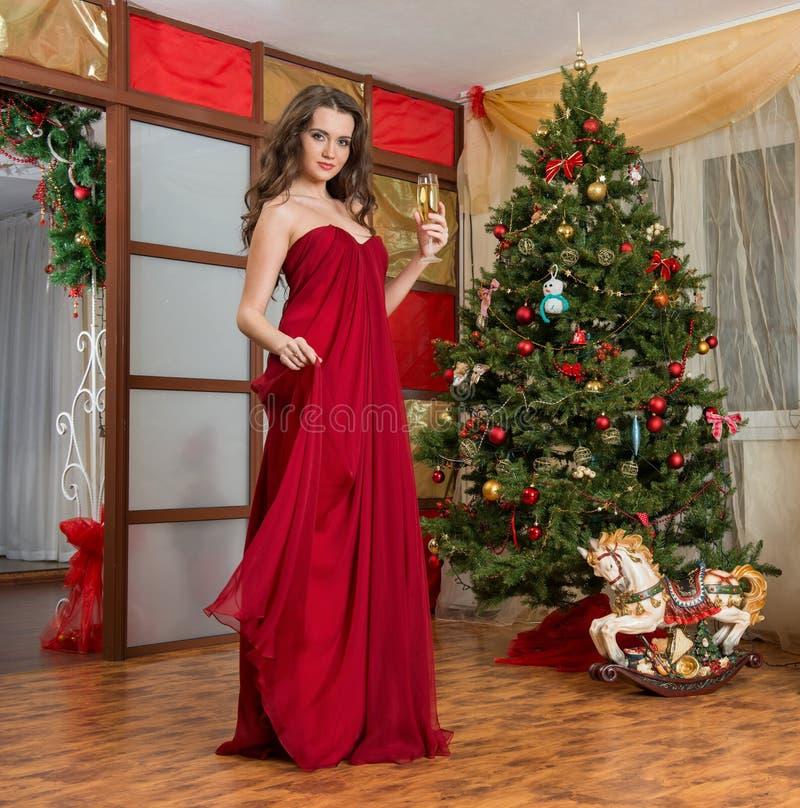 Девушка с стеклом шампанского на дереве Нового Года стоковые фотографии rf