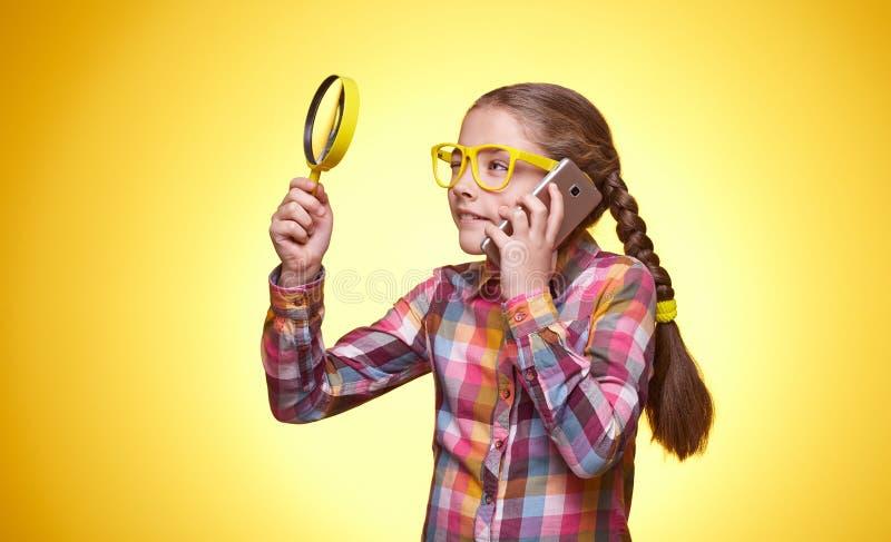 Девушка с телефоном и увеличителем на желтой предпосылке стоковые изображения