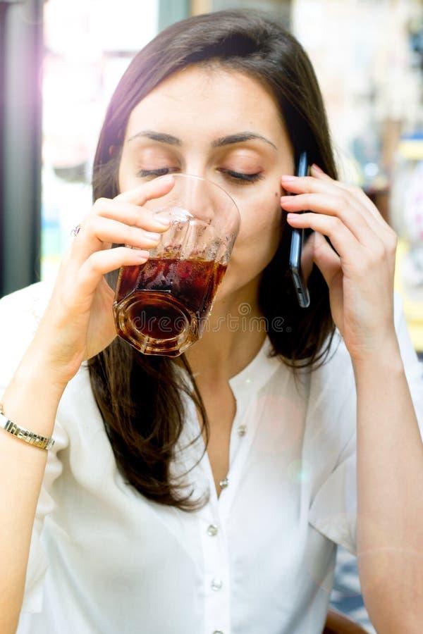Девушка с темными волосами выпивая коктеиль и говоря на телефоне стоковое изображение rf