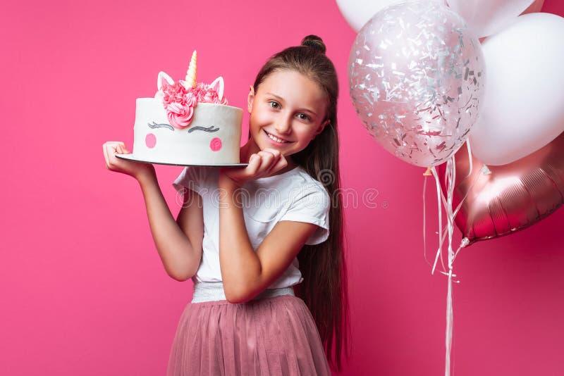 Девушка с тортом для дня рождения, в студии на розовой предпосылке, праздничное настроение, конец - вверх, дизайнерский торт стоковые изображения rf