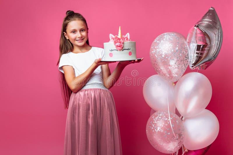 Девушка с тортом для дня рождения, в студии на розовой предпосылке, праздничное настроение стоковое фото rf