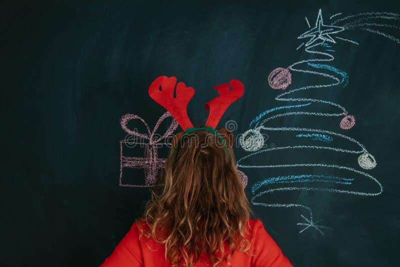 Девушка с ушами и рождеством северного оленя стоковые фото