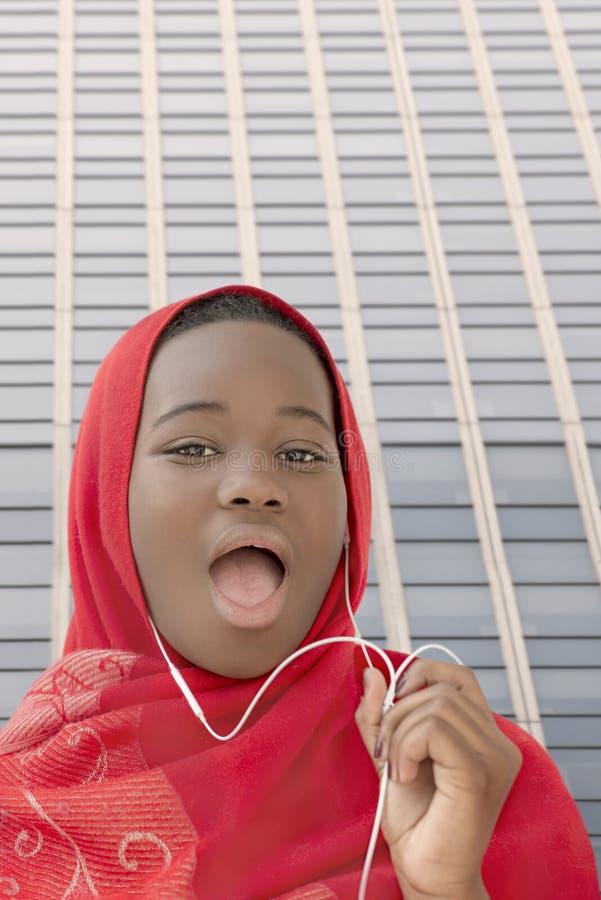 Девушка слушая к музыке и поя в улице, 13 летах старых стоковое фото