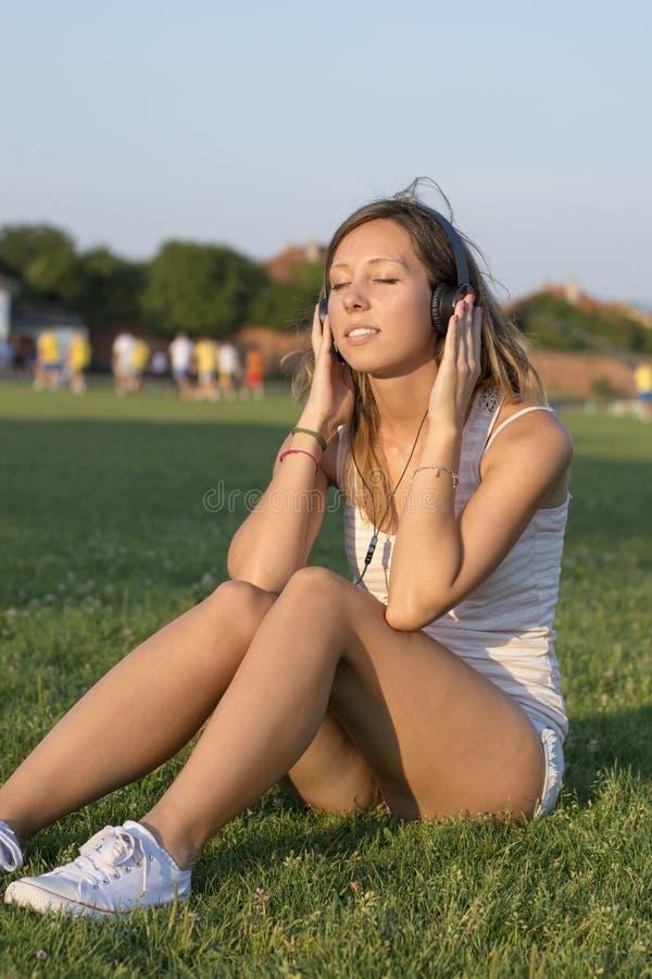 Девушка слушая к музыке на футбольном поле Тренируя пролом стоковое фото