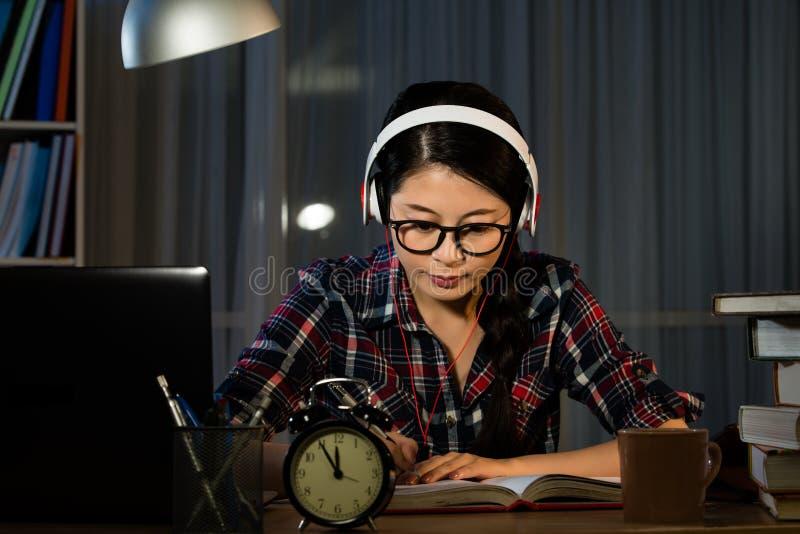 Девушка слушая к музыке пока изучающ стоковые изображения