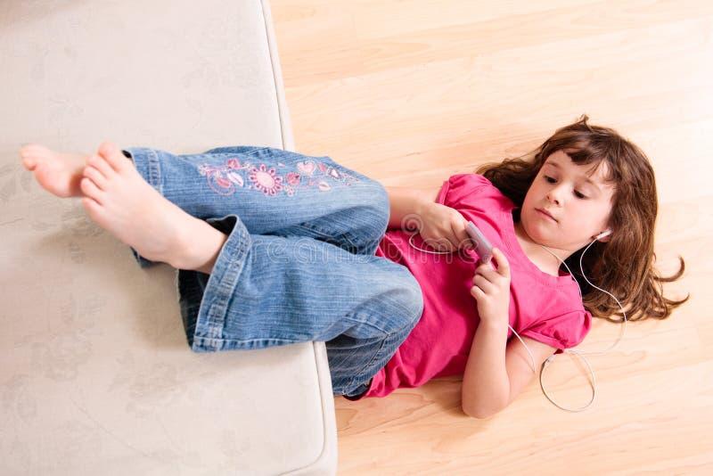 Девушка слушая к нот стоковые изображения
