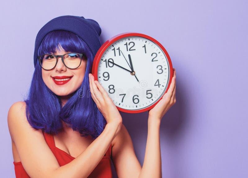 Девушка с фиолетовыми волосами и большими часами стоковые изображения rf
