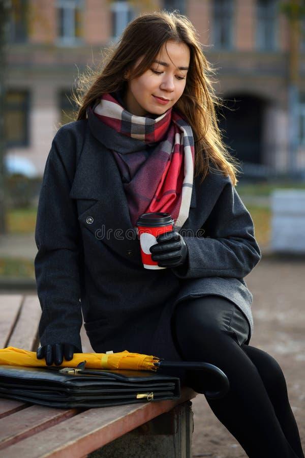Девушка с чашкой кофе на прогулке в парке стоковое фото rf