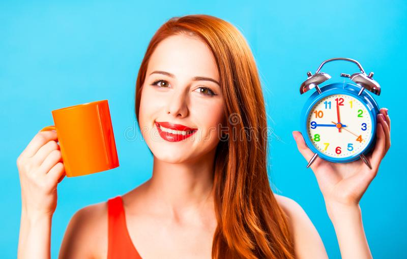 Девушка с чашкой чая и будильником на голубой предпосылке стоковые фото