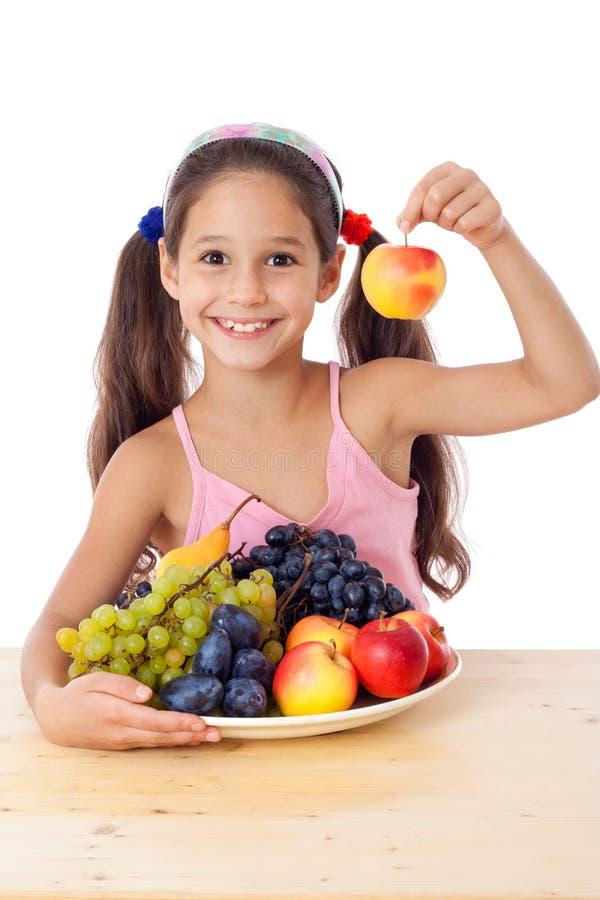 Девушка с яблоком и плита плодоовощ стоковые фото