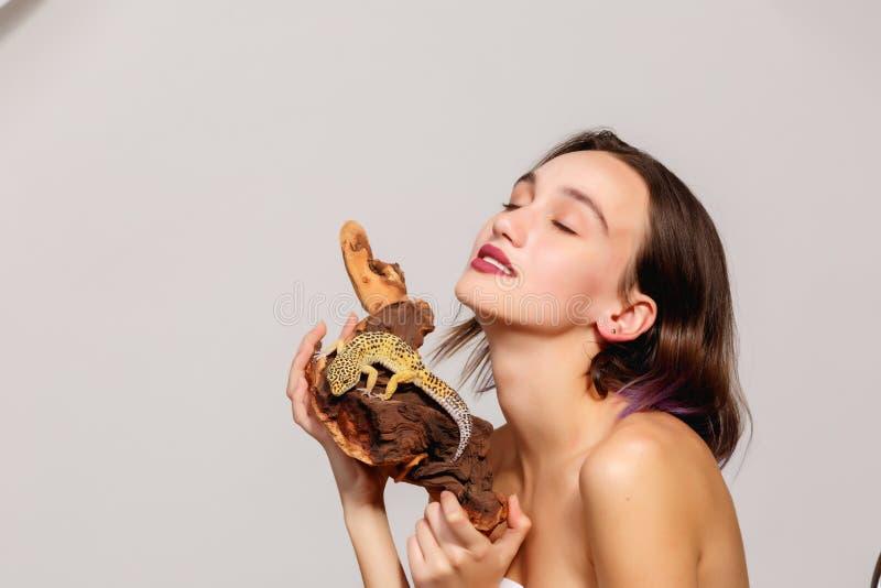 Девушка с ящерицей на серой предпосылке стоковые фото
