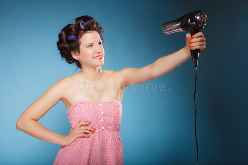 Девушка с curlers в волосах держит hairdreyer стоковое фото rf