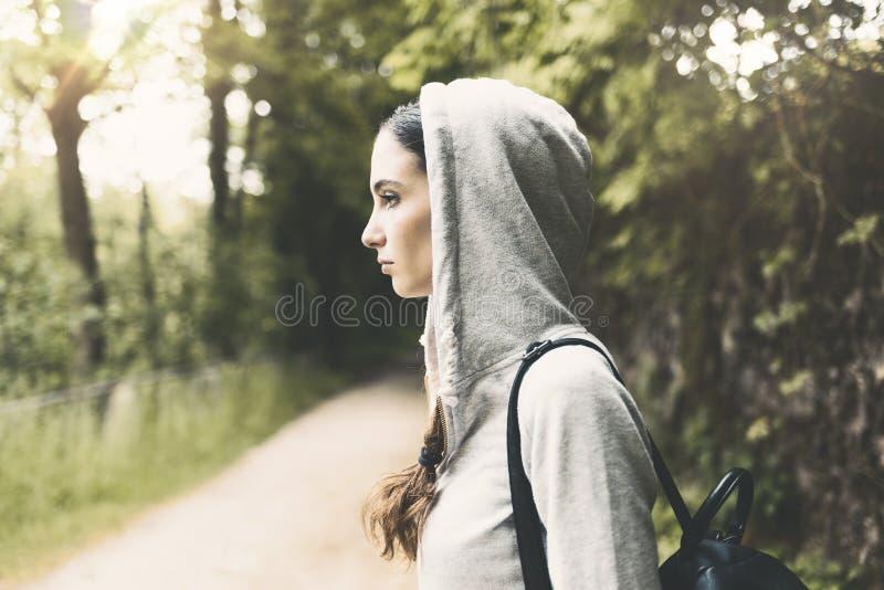Девушка с hoodie идя в древесины стоковое фото rf