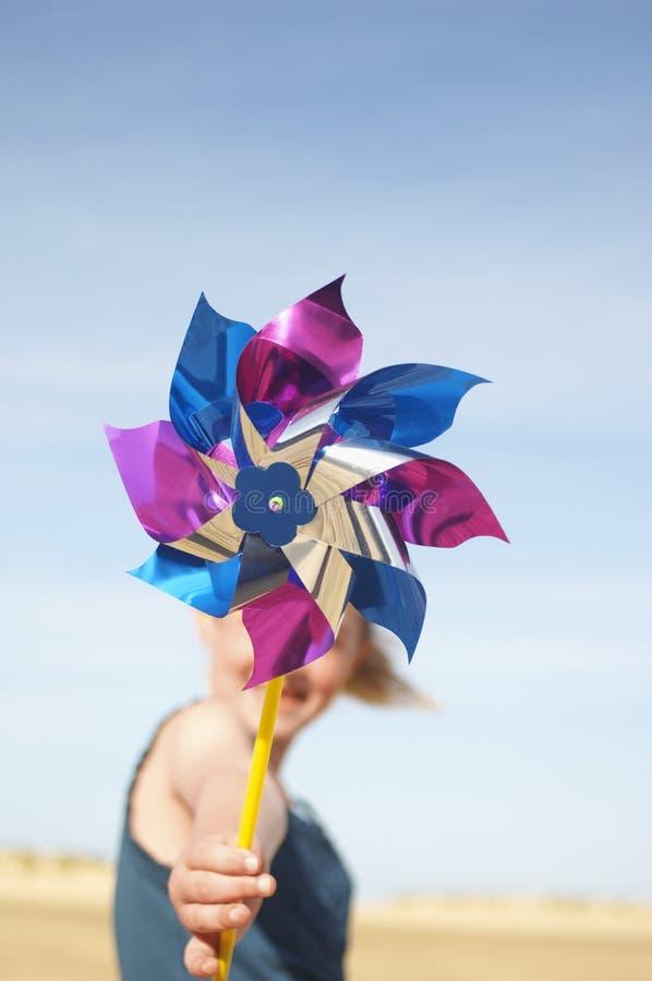Девушка с Pinwheel на пляже стоковое фото rf
