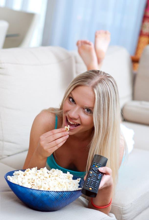Девушка с remote и попкорном стоковая фотография rf