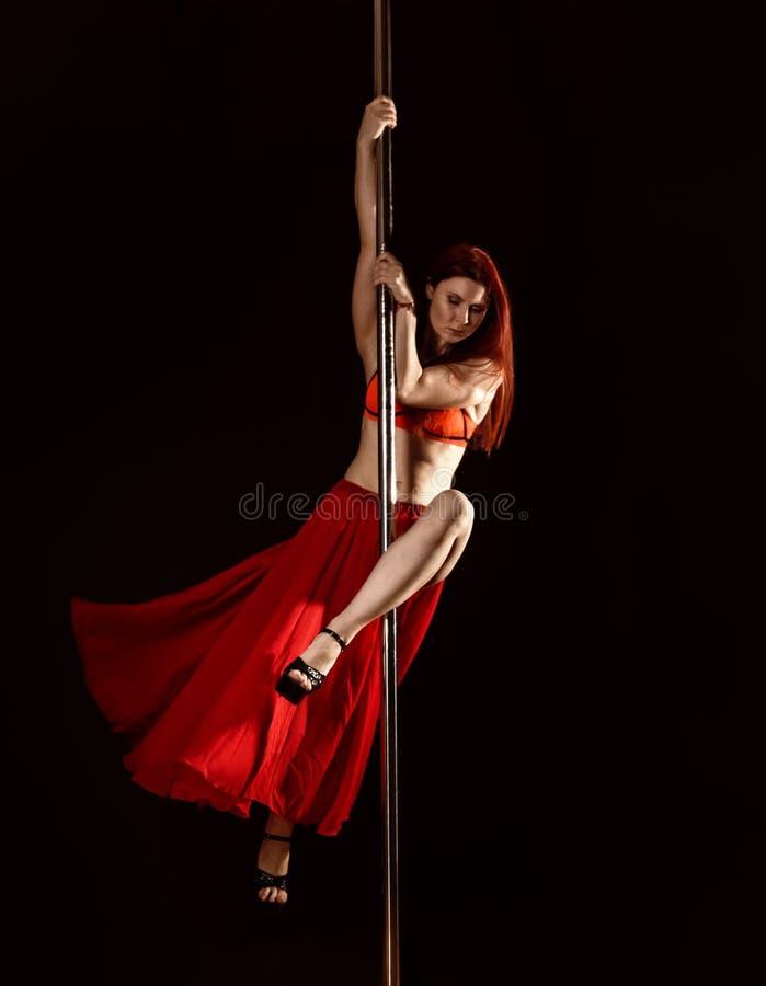 Девушка танца поляка молодого redhead атлетическая в красном платье на черной предпосылке студии стоковое фото rf