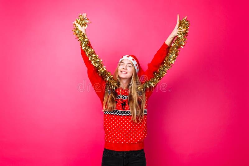 Девушка танцев в красном свитере, и шляпа Санта, имеют потеху с сусалью на шеи, празднуя Новый Год на красной предпосылке стоковые изображения rf