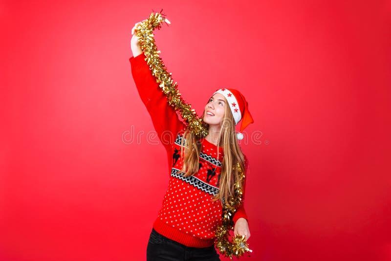 Девушка танцев в красном свитере, и шляпа Санта, имеют потеху с сусалью на шеи, празднуя Новый Год на красной предпосылке стоковое фото rf
