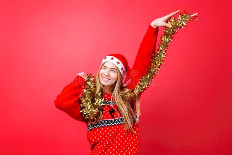 Девушка танцев в красном свитере, и шляпа Санта, имеют потеху с сусалью на шеи, празднуя Новый Год на красной предпосылке стоковые изображения
