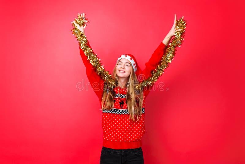 Девушка танцев в красном свитере, и шляпа Санта, имеют потеху с сусалью на шеи, празднуя Новый Год на красной предпосылке стоковая фотография rf