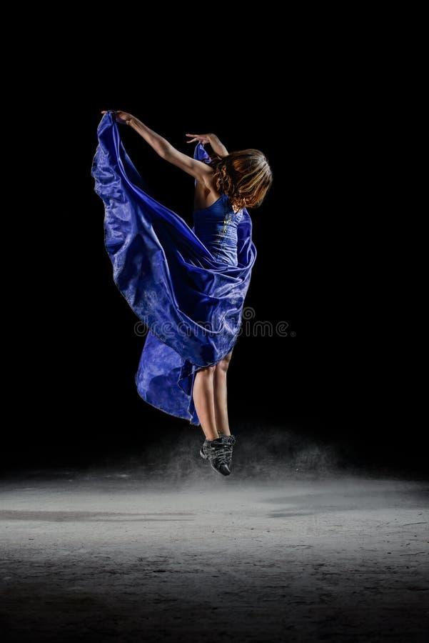 Девушка танцев в скачке темноты в пыли стоковые фото