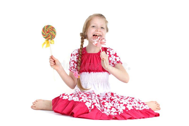 Девушка 8-ти летняя с помадкой конфеты стоковые фото