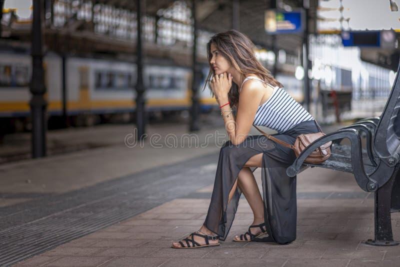 Девушка-турист терпеливо ждет на платформе поезда стоковое изображение