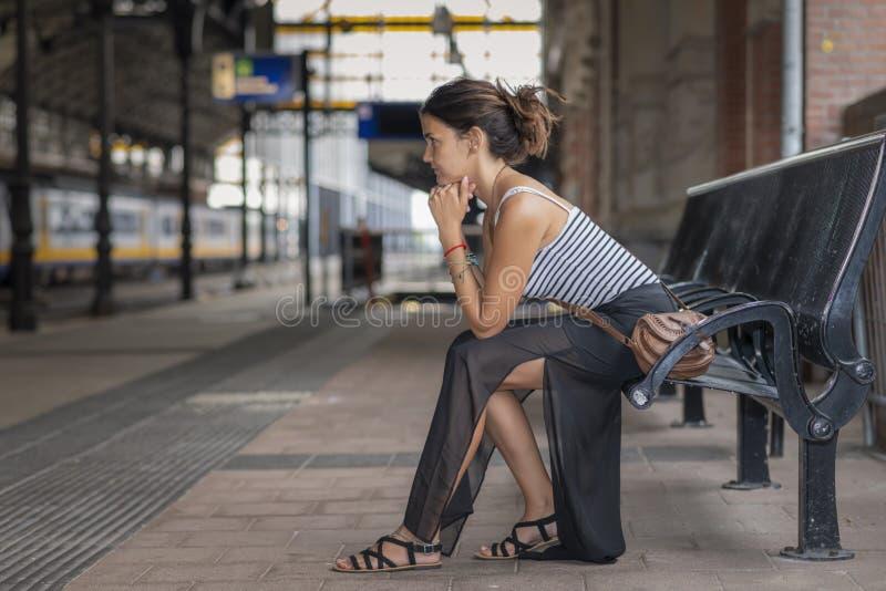 Девушка-турист терпеливо ждет на платформе поезда стоковая фотография rf