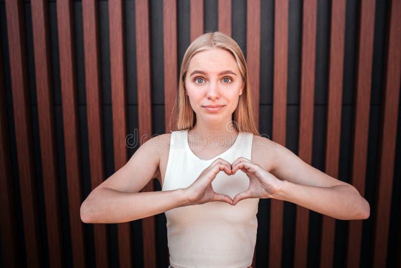Девушка уверенно и gorgeus белокурая смотрит на камере Она удовлетворена Молодая женщина показывает форму сердца с ей стоковое фото rf