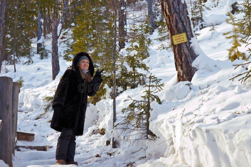 Девушка указывает к знаку с информацией о путешествованном расстоянии стоковые изображения rf