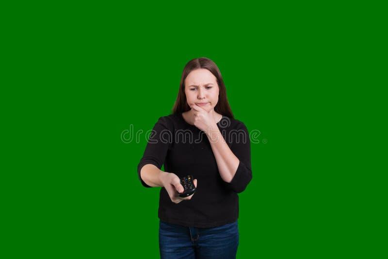 Девушка указывая дистанционное управление смутила выражение на ее стороне стоковая фотография rf