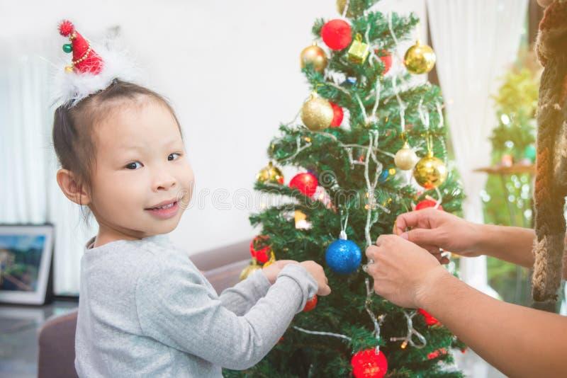 Девушка украшая рождественскую елку дома стоковое фото rf