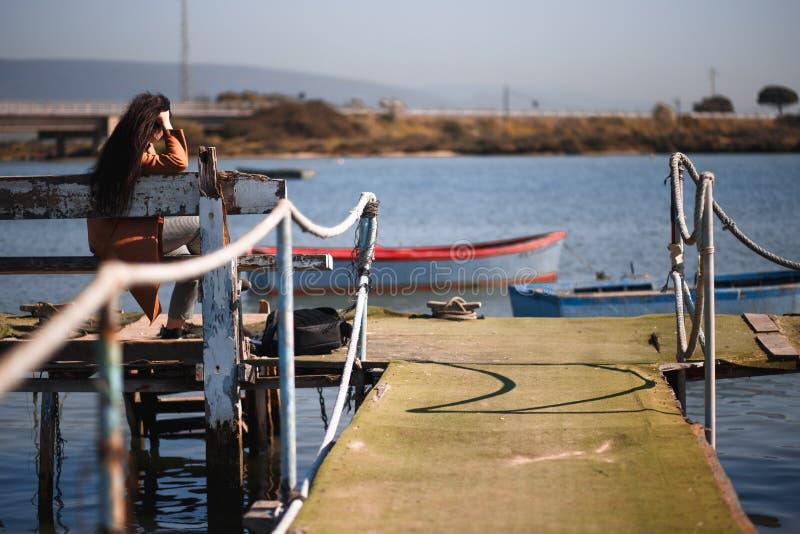 Девушка усаженная на пристань стоковое фото
