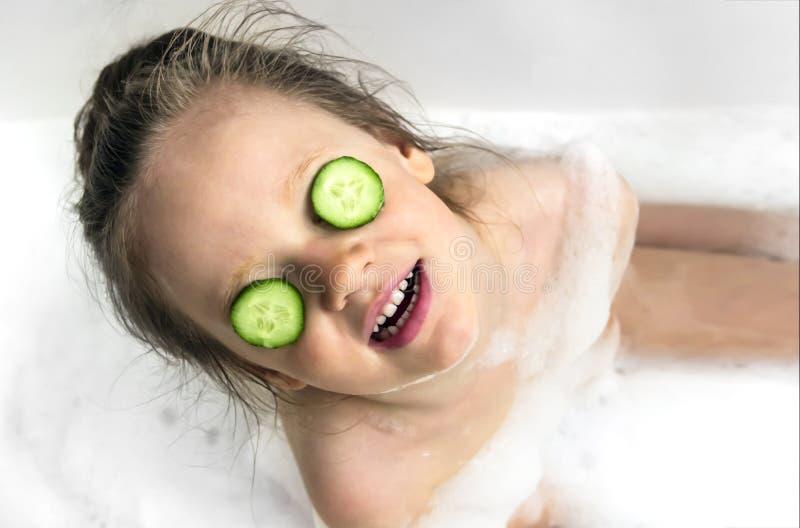 Девушка усмехается снег-белая улыбка в стороне ванной комнаты заштукатуренной с белой сливк и глаза огурец стоковое изображение