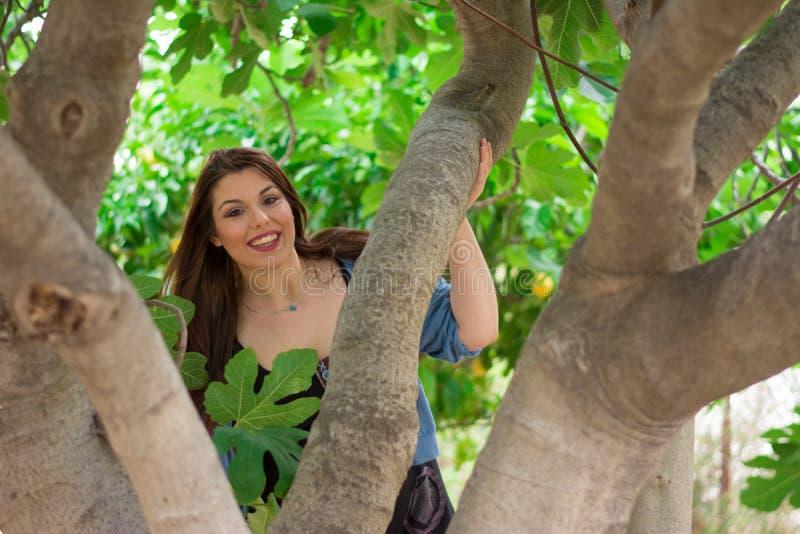 Девушка усмехаясь за смоковницей стоковое фото rf