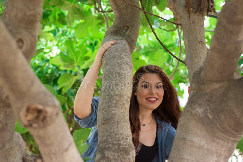 Девушка усмехаясь за смоковницей стоковая фотография