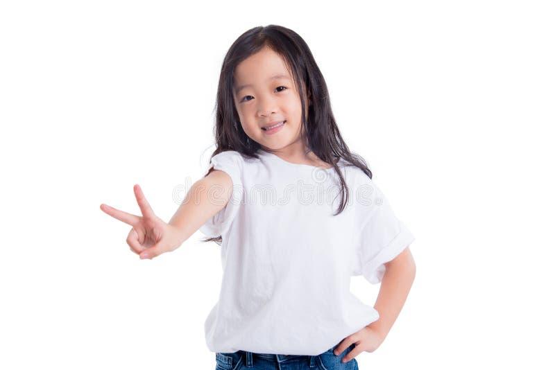 Девушка усмехаясь и делая победу жеста над белизной стоковое изображение rf