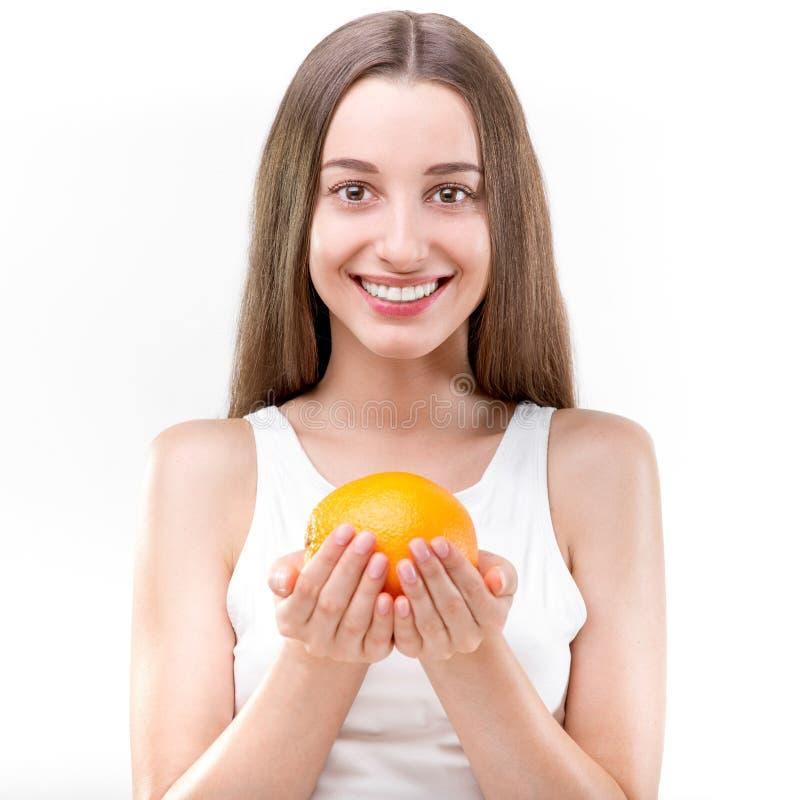 Девушка усмехаясь и держа апельсин стоковое изображение rf