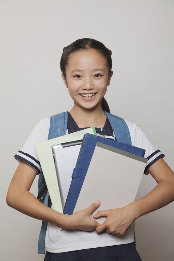 Девушка усмехаясь и держа пук тетрадей и цифровой таблетки, студии стоковые фотографии rf