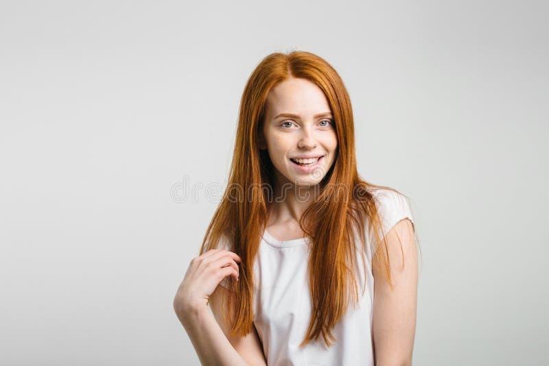 Девушка усмехаясь при закрытые глаза касаясь ее красным волосам над белой предпосылкой стоковое изображение rf