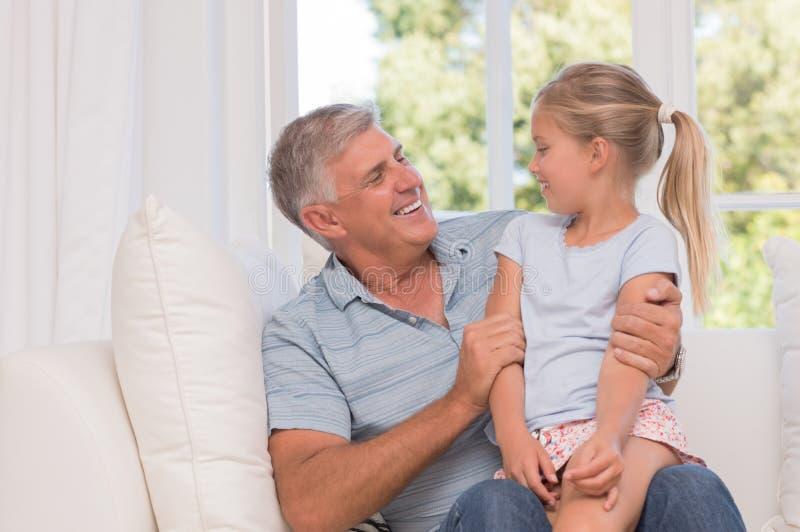 Девушка усмехаясь с дедом стоковые фото