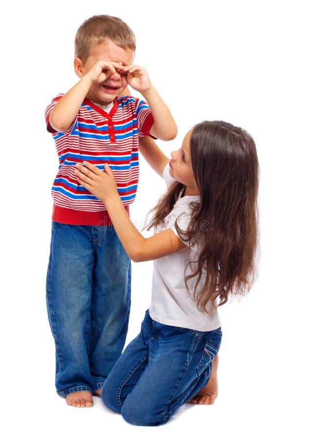 Девушка утихомиривая вниз ее маленького плача брата стоковые изображения