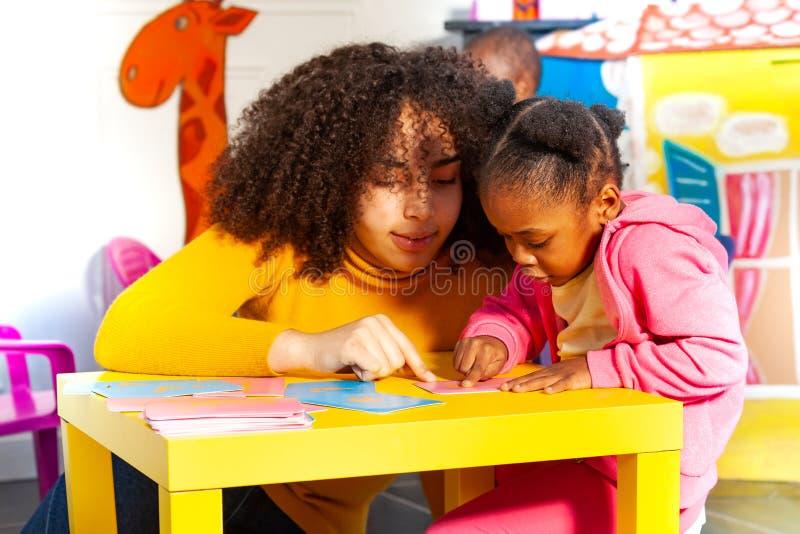 Девушка учит cursive алфавит тактильными картами стоковые изображения