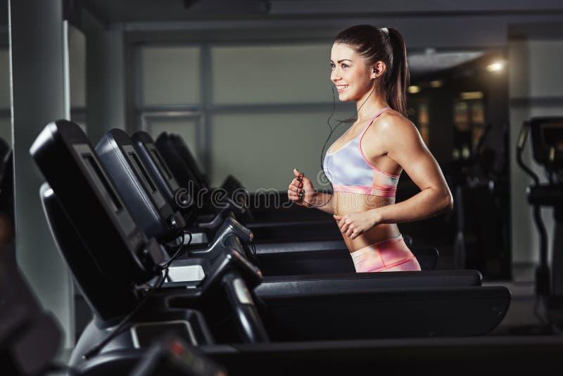 Девушка фитнеса бежать в спортзале стоковые фотографии rf
